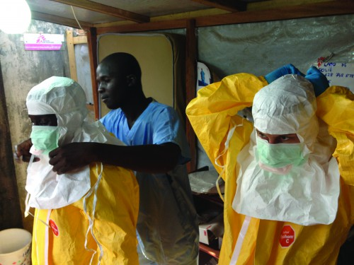 Humanitarians don protective suits to help the fight against Ebola in Guinea.